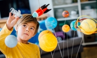 Child playing with space-related items
